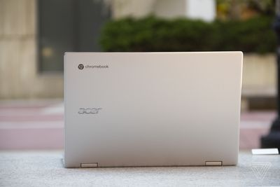 The Acer Chromebook Spin 513 open, seen from the back, on a stone bench.